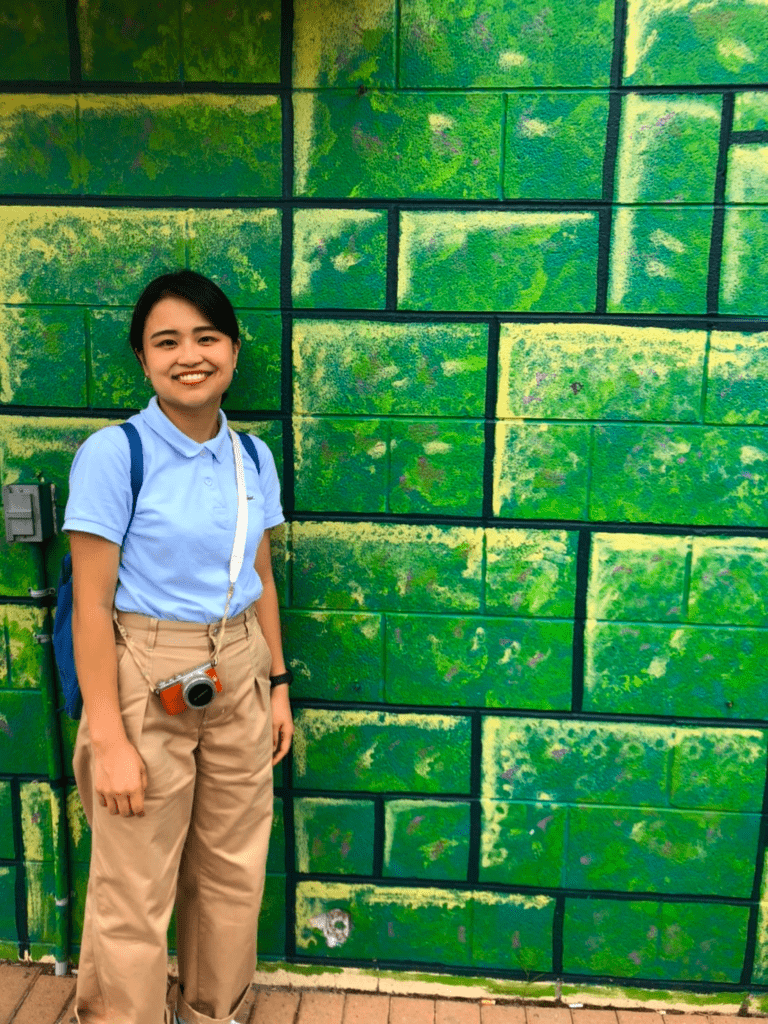 Doshisha student, Arisa Yoshimura, standing in front of a green wall