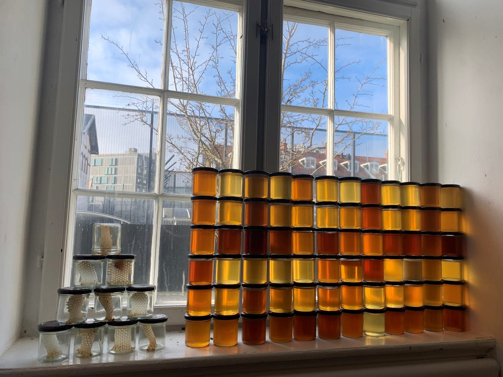 Jars of honey stacked on a windowsill