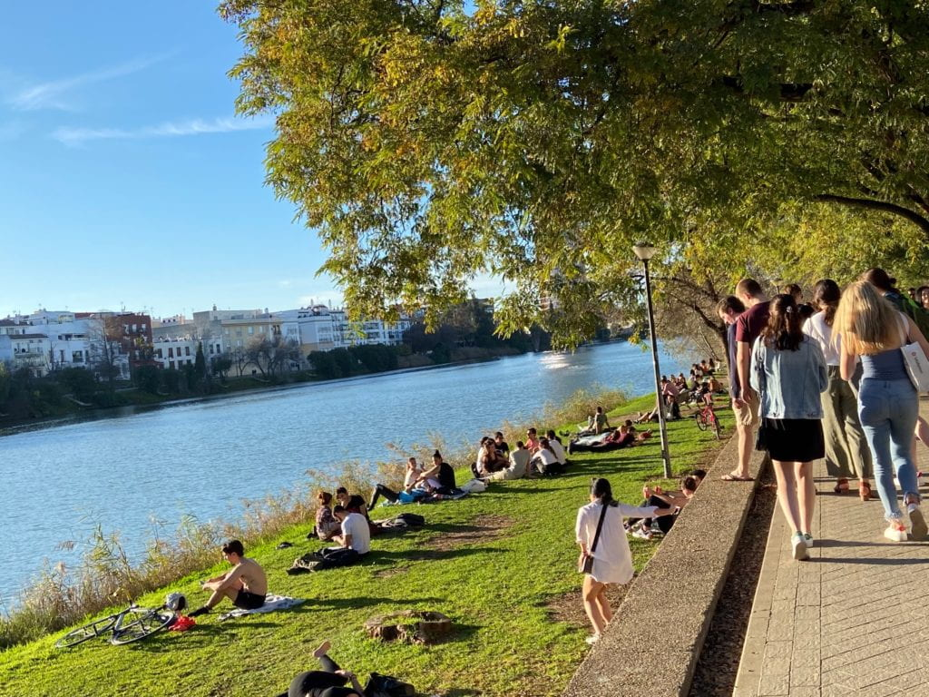 People sit on the green banks of a bright blue river