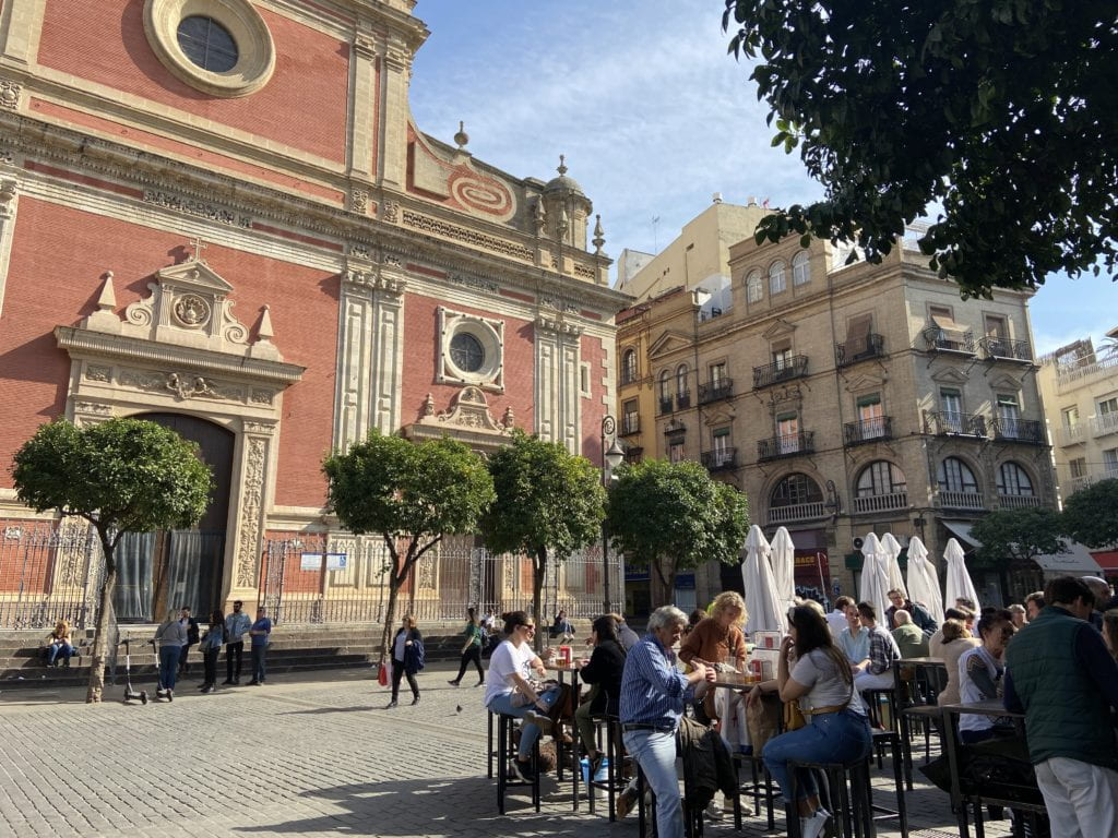 People eat at small tables in front of a pink and yellow building
