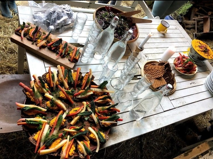 Colorful vegetables arranged on a plate with glasses of water on a picnic table