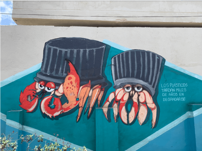 "This mural depicts crabs with to-go containers in the place of their shells. The caption says, ""plastics take thousands of years to degrade."""