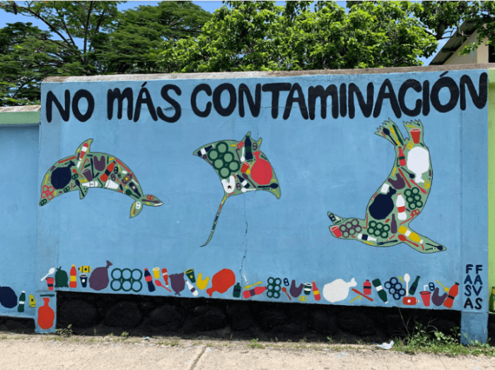 "This mural depicts three iconic Galápagos marine species - a dolphin, a ray, and a sea lion - filled with plastic. The text at the top reads: ""No more pollution."" There is a piece of litter in the lower right hand corner."