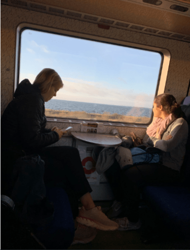 Two girls looking out the window of a train
