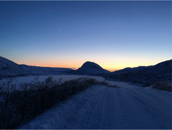 The sun sets behind a mountain with snow in the foreground