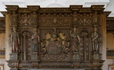Although now missing parts, the four caryatids that surround the coats of arms on the mantelpiece reflect both the values and aesthetic tastes Bodenham – a devout Catholic – wanted to present. From left to right, the four virtues are Justice (who originally held scales), Temperance (who held water and wine), Prudence (who held a mirror, book, or dove in addition to the snake), and Fortitude (who still holds a column).