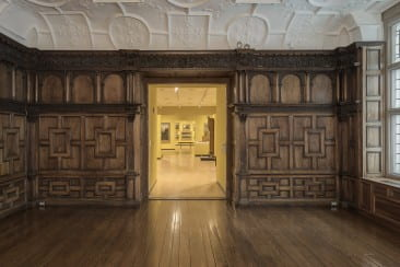 Although the mantelpiece is carved oak, the original panels are rendered from English walnut, a material that had rarely been used on such a large scale before Rotherwas. These unpainted panels, whose architectural details seek to emulate Italian Renaissance designs, demonstrate the work of several craftsmen. The arches depicted vary in width throughout the room, narrowing near the corners; these variations may represent an early attempt to heighten the room's sense of volume through the process of linear perspective.