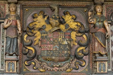 The Bodenham coat of arms, which appears in the upper left of this array of twenty-five families, would have originally featured a background of deep azure. In heraldic terms, the crest consists of a horizontal stripe (called a fess) between three chess rooks, all rendered in gold. The identities of the remaining twenty-four family crests are not all certain, and some may even have been fabricated in order to visually amplify Bodenham's status.