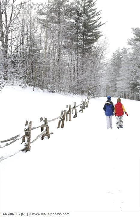 Two boys walking in the snow along a wooden fence