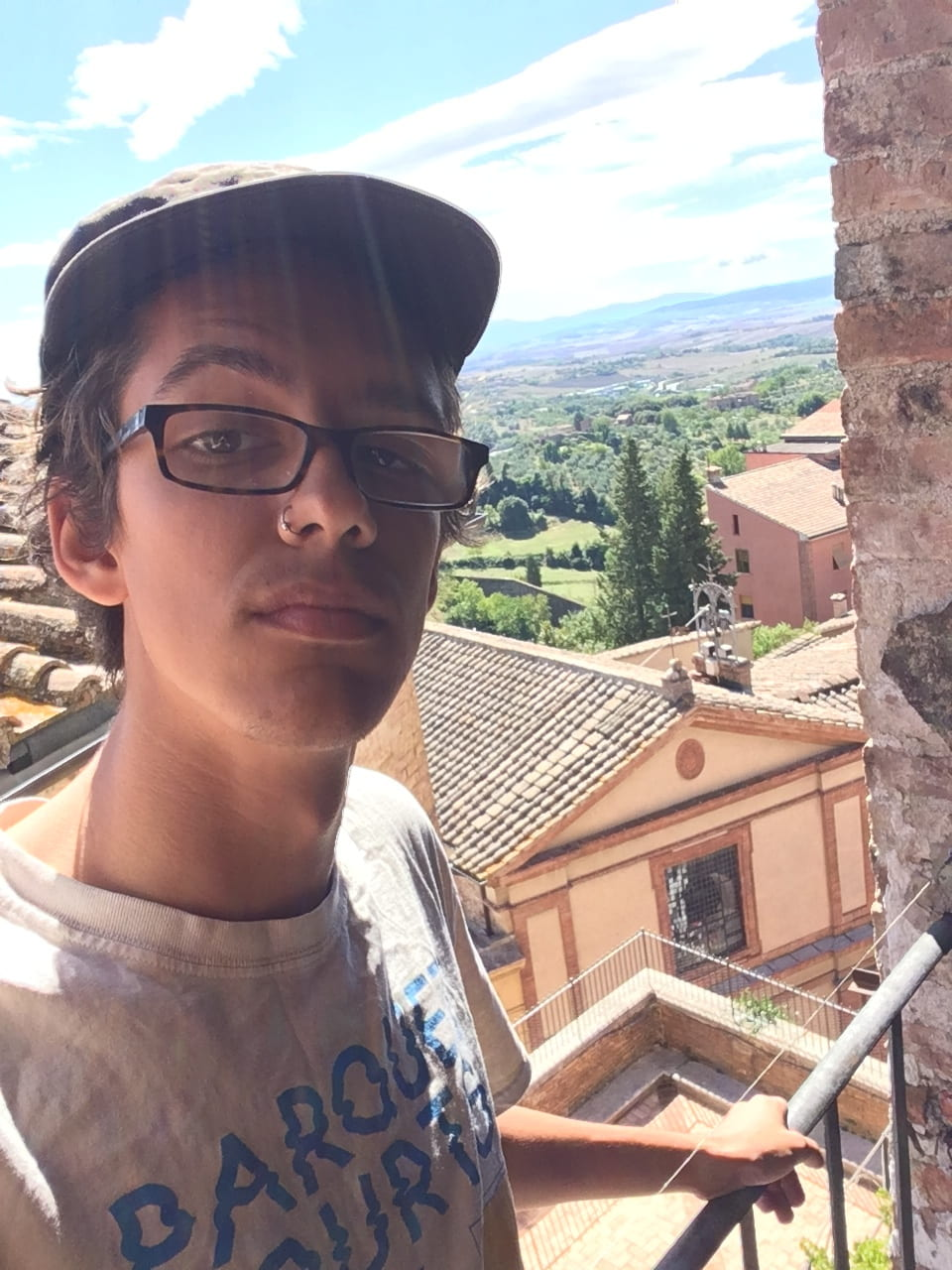 Handsome young man standing before Tuscan landscape