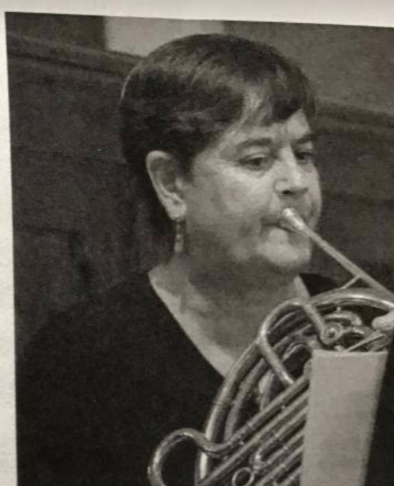 Fleur Barnes-Rowell, sitting, playing horn