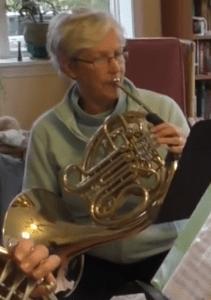 Margot Rowland sitting, playing horn