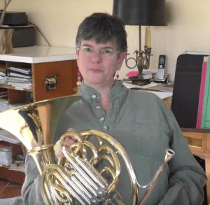 Christine Mortensen sitting, holding horn, smiling