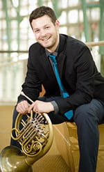 Josh Michal sitting with french horn, smiling, indoors