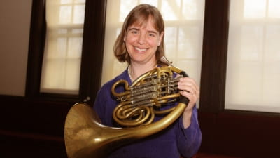 Jean Jeffries standing with french horn, indoors, smiling
