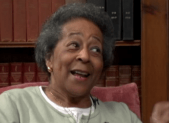 An African-American woman with grey hair smiles as she looks off-camera towards her interviewer. She is wearing a green sweater and sits in an armchair. Bookshelves fill the wall behind her.
