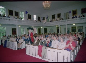 Alumni sit in pews in Johnson Chapel, watching a costumed mascot dance. He is a British soldier with white curly hair, wearing a tricorn hat, a red jacket, and blue trousers. The mascot head is about four times the size of a human head.