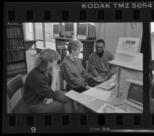 A photograph of 3 people sitting at a table in front of a computer.