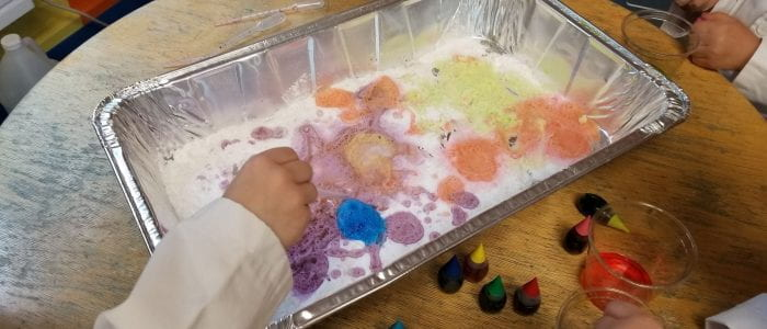 Outreach demo picture. Baking soda with colored vinegar being pipetted onto it by the kids.