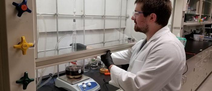 Shea Martin working in the chemical fume hood.