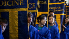 Peer academic advisers hold school banners
