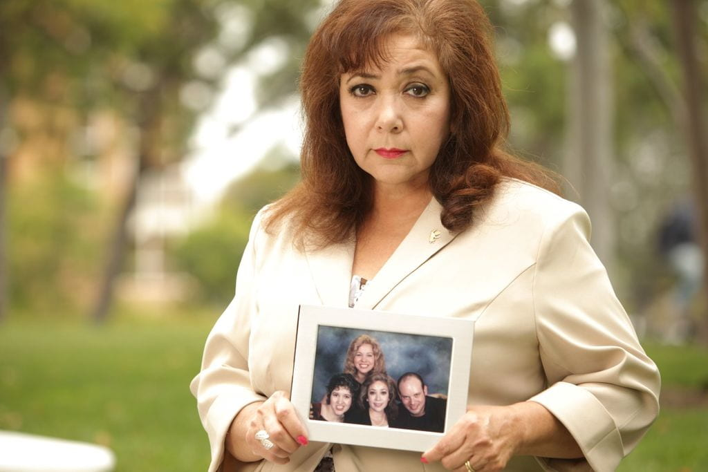 Frances Saldaña with a photo of her family