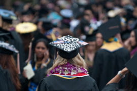 A graduate with a thank you on their mortarboard