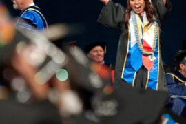 A graduate celebrating at Social Ecology Commencement