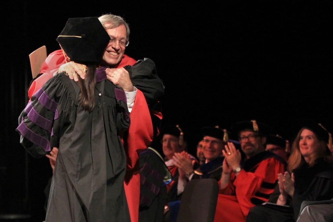 Dean Erwin Chmerinsky hugs graduate Jean Su
