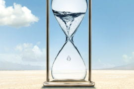 Hourglass holding water sitting in a desert