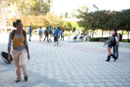 Santana laughing with a friend on the way to class