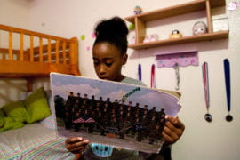 Nyla reads the notes from fellow soldiers on her mom's group photo from basic training