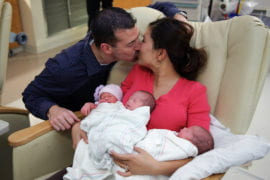 Steven gives Angie a kiss while the triplets sleep in her arms