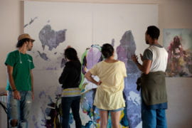 Mural contributors discuss the upside down and inverted world map.