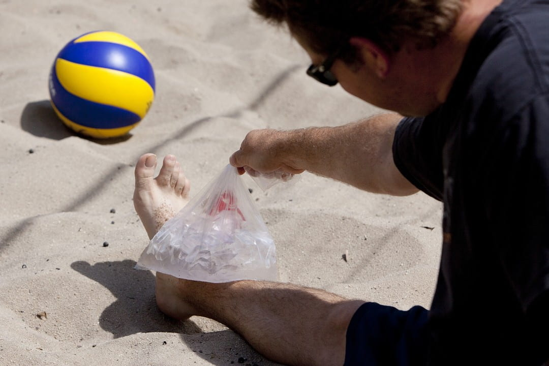 Beach volleyball player icing their ankle