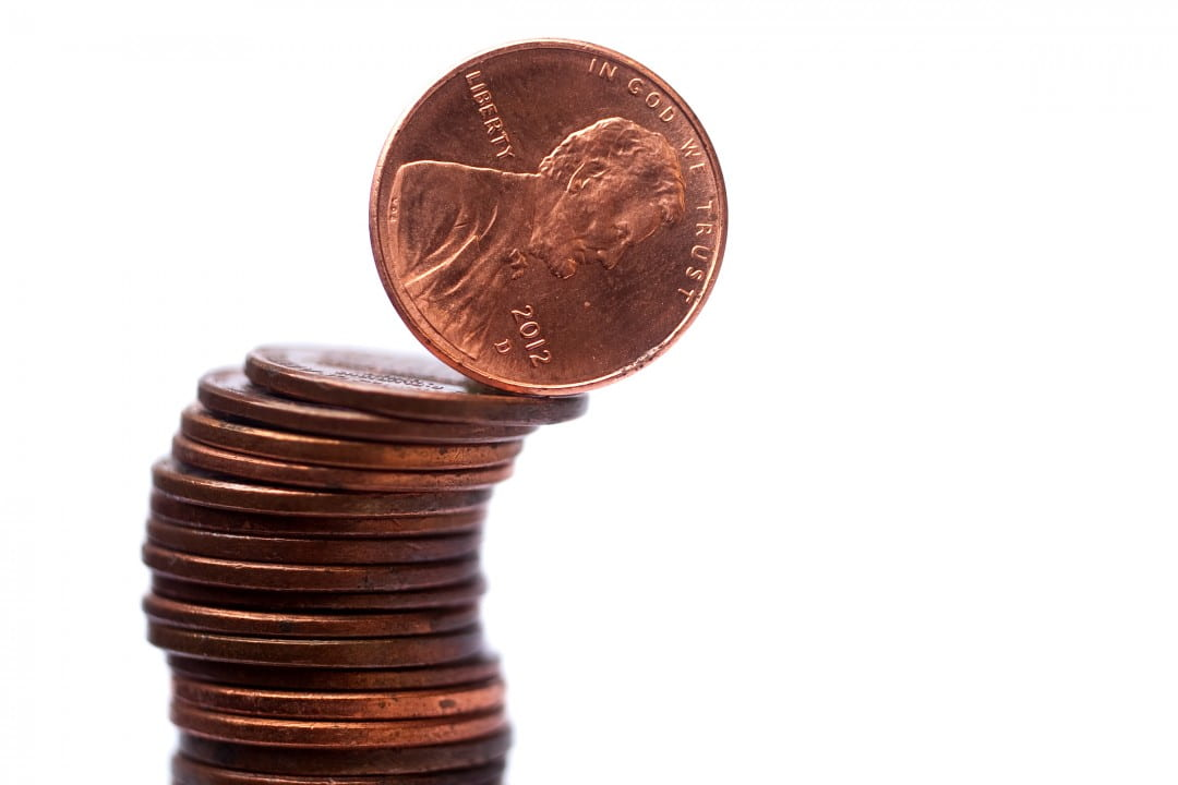 Stacked pennies about to topple