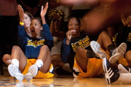 Two basketball players cheering on the court