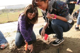 Lauren Wong helps Luiseno tribe member Grace Galvin plant a garden on the reservation