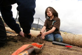 Little Luiseno Ricky Galvin lends a hand to UCI students planting a garden