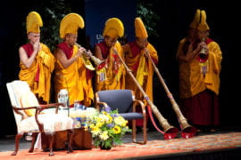 Buddhist monks play traditional Tibetan horns