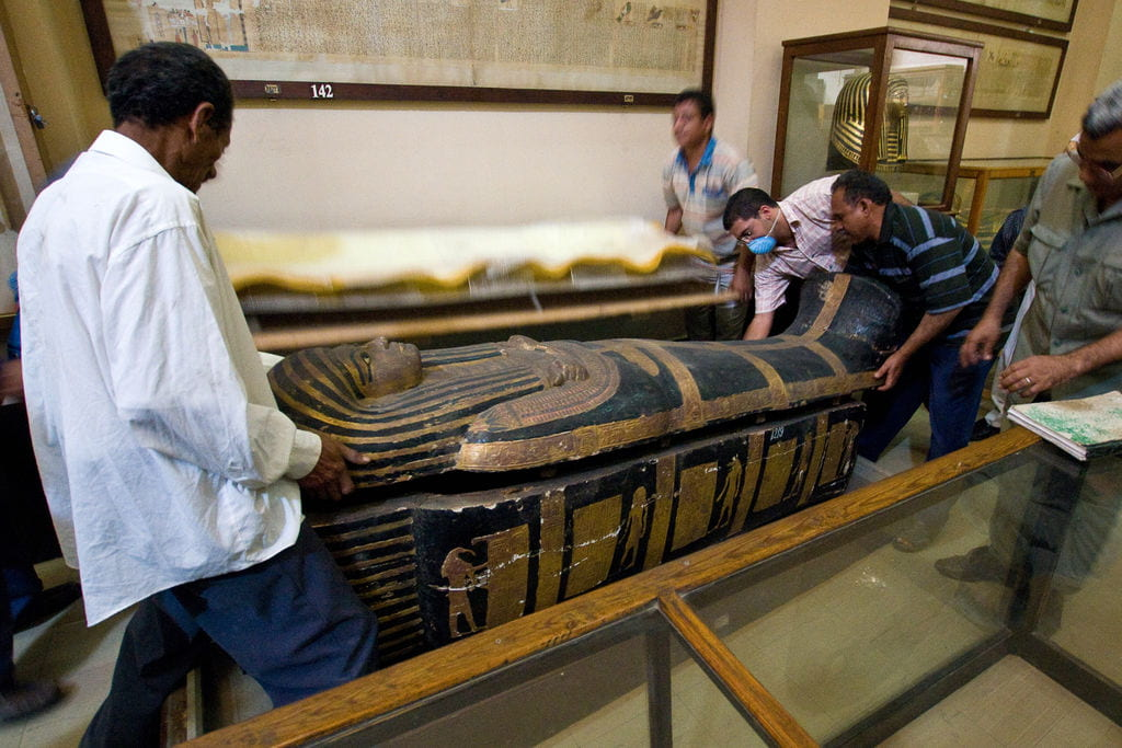 American and Egyptian researchers carrying a sarcophagus