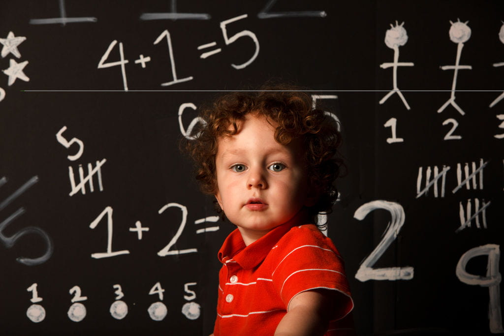 A child in front of a blackboard with math problems on it