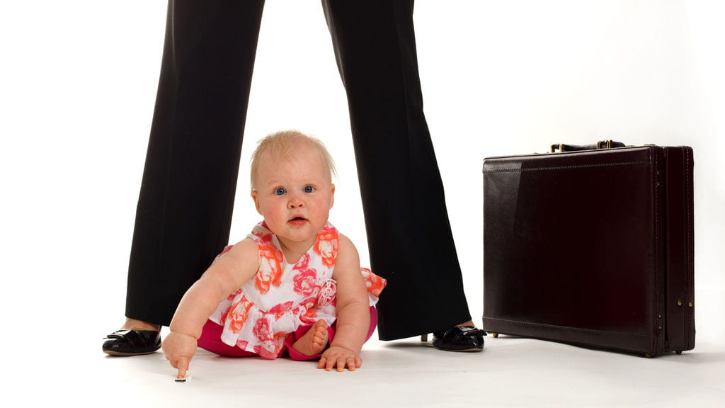 Baby sitting at the feet of their mother next to a briefcase