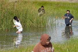 students wade through the San Joaquin Freshwater Marsh Reserve