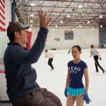 Zhou gets some pointers from coach Alex Chang