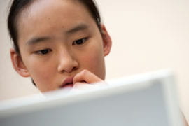 Zhou studies with her laptop at the Student Center