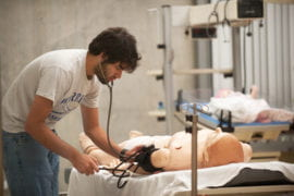 Colin McCrimmon performs a vital signs test on a medical simulation patient