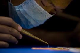 A Tibetan Buddhist monk creates a sand mandala