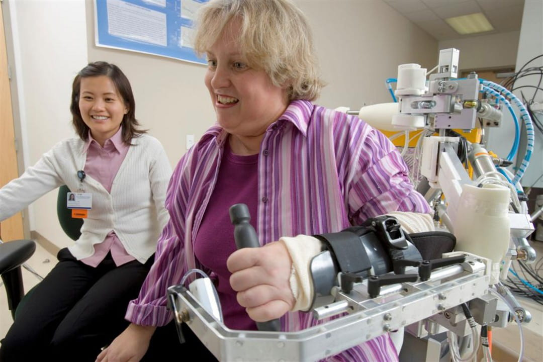 Patient using the robotic arm for rehab