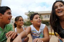Dana Aryan plays with local children